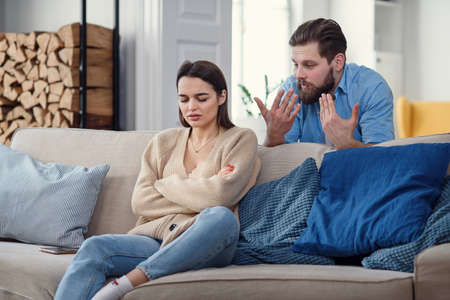 Photo pour Offended angry woman sits on sofa at home after an argument with her husband. Broken marriage. - image libre de droit