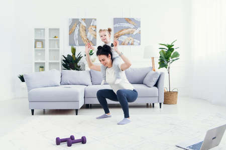 Photo pour Beautiful mommy and charming little daughter are smiling while doing fitness exercises together at home. - image libre de droit