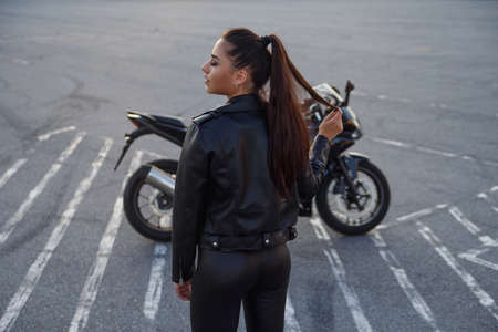 Photo pour girl with long hair in a leather jacket in an underground parking lot on a motorcycle - image libre de droit