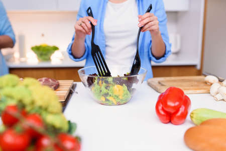 Photo for Close up photo of young womans hands mixing fresh vegetables salad in a glass plate at the kitchen. - Royalty Free Image