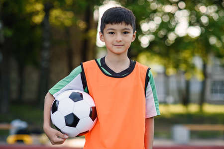Photo pour Confident teen football player in orange vest holds a ball in hand after training on outdoors sports field at morning. - image libre de droit