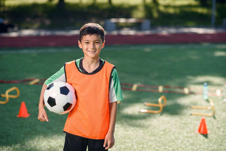 Photo pour Cute asian boy in soccer uniform with ball after productive training on artificial football stadium on summer day. - image libre de droit
