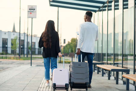 Photo pour Stylish multiracial couple carrying their suitcases on wheels going to the airport direction. - image libre de droit