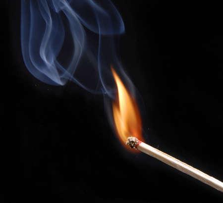 Lit match with smoke on black
