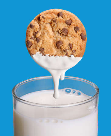 Portrait of chocolate chips dip into a glass of milk