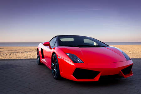 Expensive red sports car at beautiful sunset