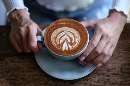 Photo pour girl holding latte coffee in cafe - image libre de droit
