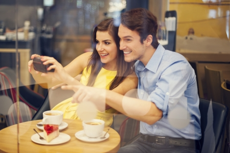 Photo pour Happy couple taking photo in cafe  - image libre de droit