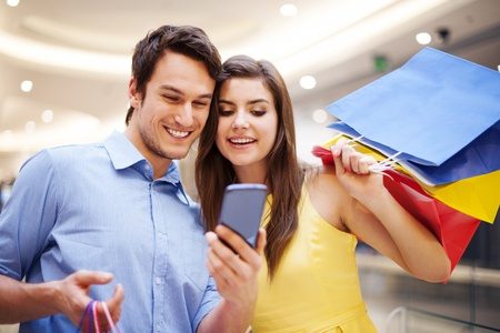 Photo pour Smiling couple checking something on the mobile phone - image libre de droit