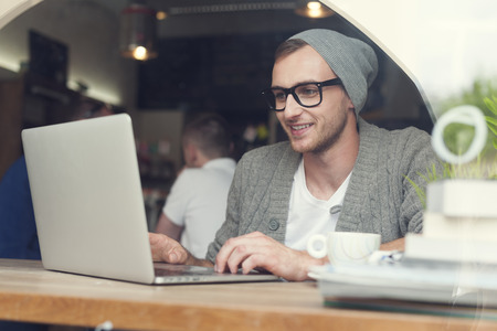 Handsome hipster using laptop at cafe