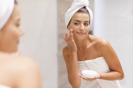 Photo pour Gorgeous woman applying moisturizer on face - image libre de droit
