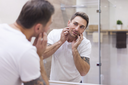 Man check condition of his skin in mirror reflection