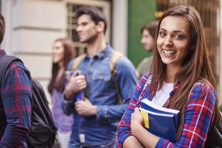 Photo pour Female student holding her books - image libre de droit