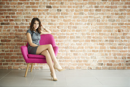 Elegant woman in the pink armchair