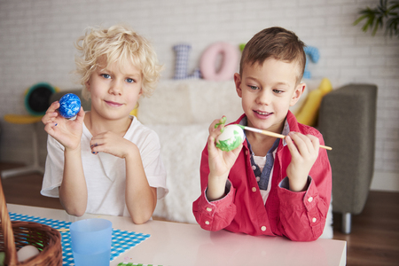 Photo for Two happy boys painting eggs for easter time - Royalty Free Image