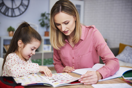 Photo pour Mother helping her daughter with homework - image libre de droit