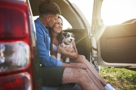 Foto de Loving couple with dog enjoying the view in summertime - Imagen libre de derechos