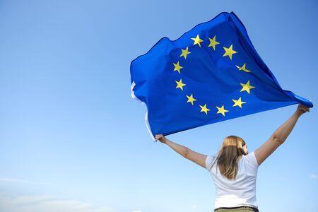 Photo pour Rear view of young woman waving the European Union flag - image libre de droit