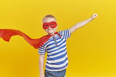 Photo pour Portrait of playful boy in superhero costume - image libre de droit