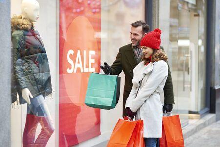 Foto de Happy couple looking at big shop display - Imagen libre de derechos