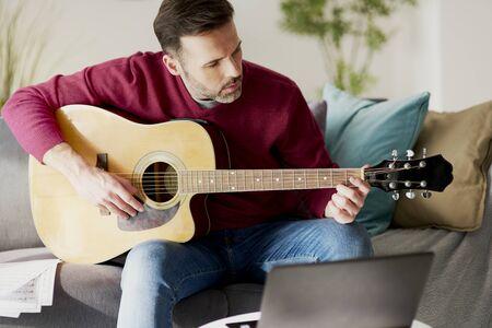 Photo pour Mid age man playing an acoustic guitar - image libre de droit