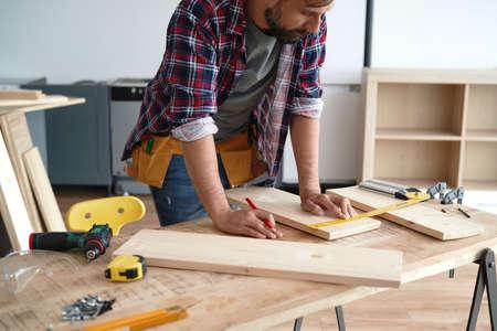 Photo pour Carpenter measures the boards at the table - image libre de droit