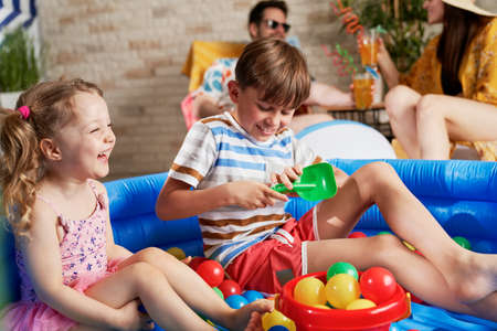 Photo pour Laughing children having fun in an inflatable ball pool - image libre de droit