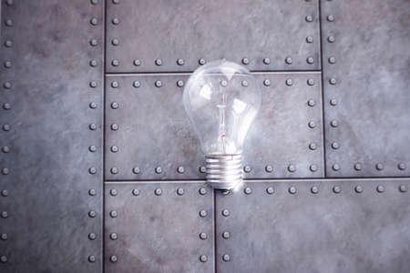 Photo pour An electric glass bulb lies on a gray iron background. Free space for text. - image libre de droit