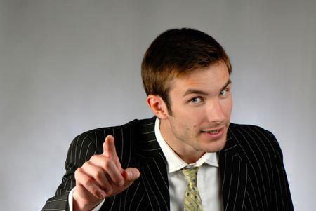 businessman emotionally gesticulates hands on  grey background