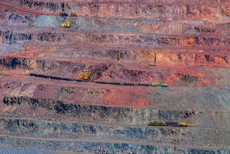 Photo pour Open pit iron ore mining. Loading of mined ore and delivery by rail and dump trucks. Ukraine. Europe. - image libre de droit