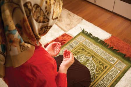 Muslim woman is praying in the house.Muslim woman praying.