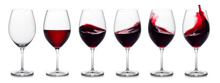 row of red wine glasses, full, empty and with splashes.