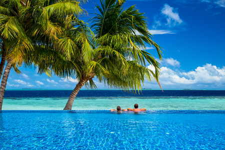 Photo for young couple relaxing in infinity pool under coco palms in front of tropical  landscape - Royalty Free Image