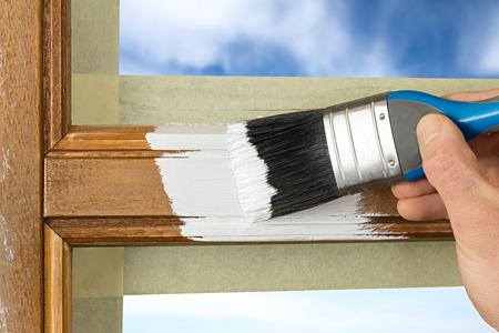 Photo pour pinting a window frame with white color - image libre de droit