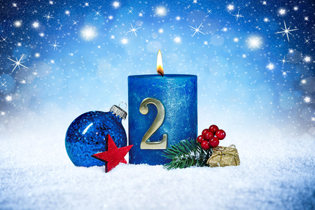 Foto de second sunday of advent blue candle with golden metal number red decoration one on wooden planks in snow front of silver panorama bokeh background - Imagen libre de derechos