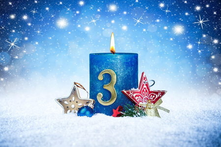 Foto de third sunday of advent blue candle with golden metal number red decoration one on wooden planks in snow front of silver panorama bokeh background - Imagen libre de derechos