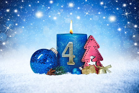 Foto de fourth sunday of advent blue candle with golden metal number red decoration one on wooden planks in snow front of silver panorama bokeh background - Imagen libre de derechos
