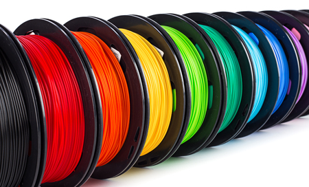 Foto de colorful bright wide panorama row of spool 3d printer pla abs filament plastic material isolated on white background - Imagen libre de derechos