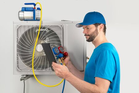 Photo for Installation service fix  repair maintenance of an air conditioner outdoor unit, by cryogenist technican worker evacuate the system with vacuum pump and manifold gauges tablet in blue shirt and baseball cap - Royalty Free Image