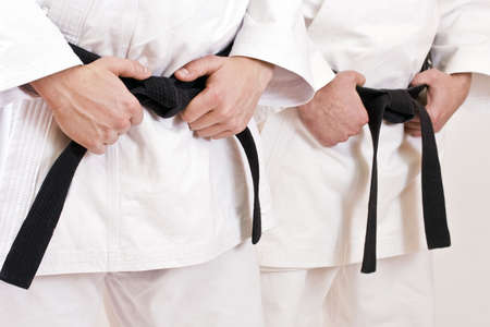 Two martial arts athlete tying the knot to his black belt