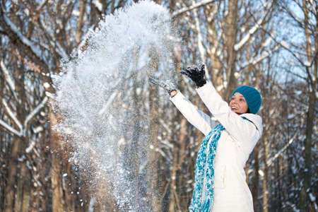 Woman throwing some snow in the air in park
