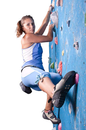 Athletic girl climbing on an indoor rock-climbing wall