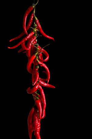 String of fresh peppers hanging on black background
