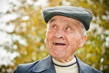 Outdoor portrait of smiling elderly man in hat