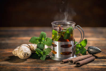 Cup of herbal tea with fresh mint on wooden table
