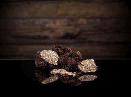 Photo pour Black autumn truffles on dark clipping path background - image libre de droit