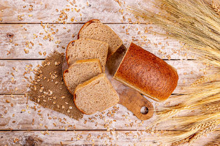 Photo pour Top view of sliced wholegrain bread on wooden background - image libre de droit