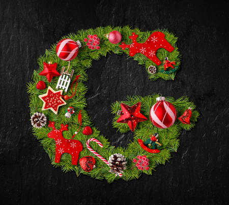 Foto de Letter G made of Christmas tree ornaments on a black slate background - Imagen libre de derechos