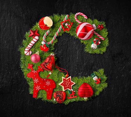 Foto de Letter C made of Christmas tree ornaments on a black slate background - Imagen libre de derechos