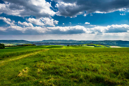 Photo pour Rural Landscape With Sunlit Clouds In Front Of The Skyline Of Vienna In Austria - image libre de droit